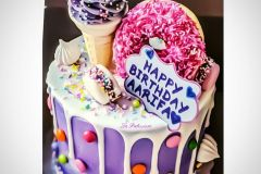 A candy Birthday cake with a n ice-cream and donut ring.
